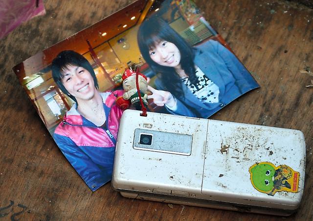 川谷清一さんがJR清水浜駅の近くで見つけた写真と携帯電話=2011年4月13日、宮城県南三陸町、川谷さん撮影