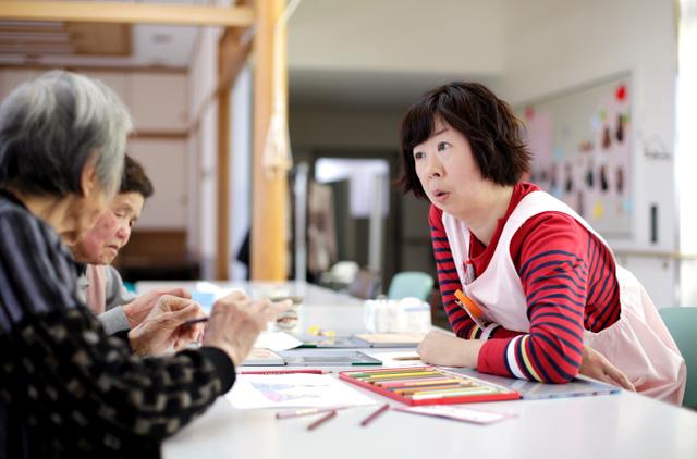 「やまゆり荘」でお年寄りと塗り絵をしながら話す渡辺久美子さん=2月25日、福島県楢葉町、関田航撮影