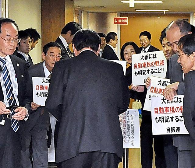 自民党税調の会合に向かう議員に、自動車業界関係者らが「減税」を訴えかける=15年12月8日、東京・永田町の自民党本部、牧内昇平撮影