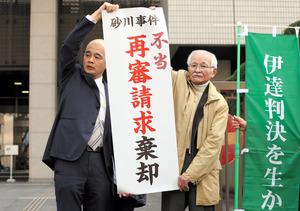 砂川事件の再審請求で「棄却」と書かれた幕を掲げる弁護士と支援者=8日午前11時3分、東京都千代田区、関田航撮影