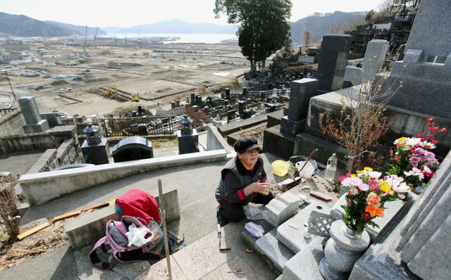 津波で亡くなった姉夫婦の墓前に花を供える小笠原スエさん(73)。眼下では復興工事が続く。「スピードが遅いよね。人がいなくなって帰って来ない。寂しすぎる」とつぶやいた=11日午前9時13分、岩手県大槌町、川村直子撮影