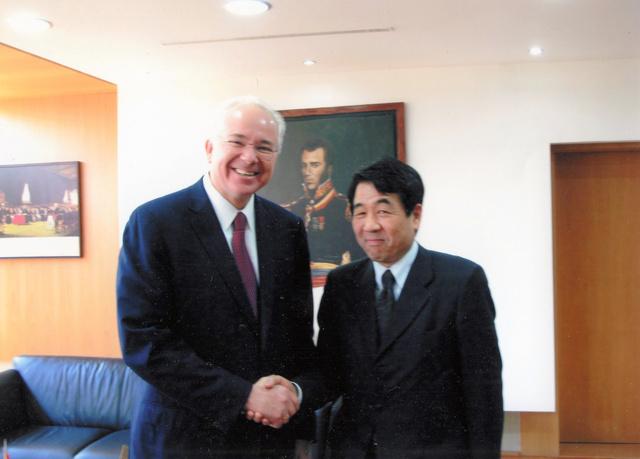 ベネズエラのラミレス石油・鉱業相(当時)と握手する徳地さん(右)。チャベス大統領(故人)らと中国企業が開発する住宅街を視察したことも=2011年3月、ベネズエラ・カラカス、徳地さん提供