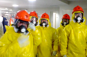 防護服の上に黄色い雨がっぱを着込み、全面マスクの上にオレンジ色のヘルメットの装備で事故収束の作業にあたった陸上自衛隊郡山駐屯地の隊員ら=2011年3月12日、東京電力の福島第一原発
