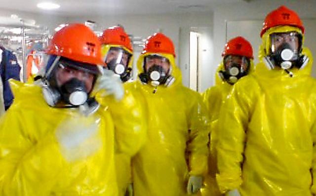 防護服の上に黄色い雨がっぱを着込み、全面マスクの上にヘルメットの装備で事故収束の作業にあたった陸上自衛隊郡山駐屯地の隊員ら=2011年3月12日、東京電力の福島第一原発