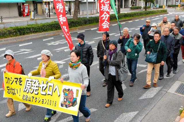 「原発ゼロへ」と書かれた横断幕を掲げてデモ行進する参加者ら=和歌山市雑賀屋町東ノ丁