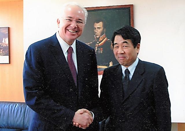 ベネズエラのラミレス石油・鉱業相(当時)と握手する徳地さん(右)=2011年3月、ベネズエラ・カラカス、徳地さん提供