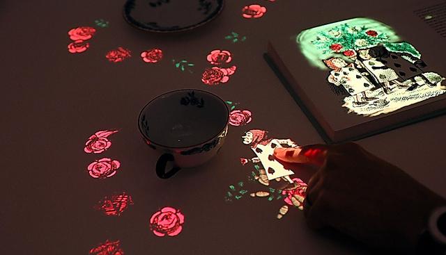 絵本(右上)から飛び出したトランプ兵をカップのそばに指でドラッグすると、バラの花が現れるプロジェクター=テキサス州オースティン、金川雄策撮影