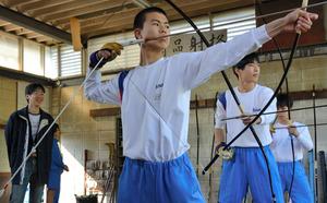 練習に取り組む弓道部の大倉倫太郎部長(手前)らを見守るコーチの山本豊さん(左端)=静岡県島田市金谷栄町