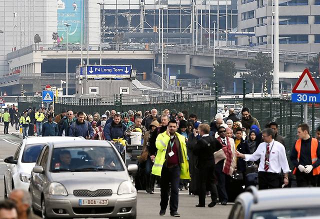 22日、爆発のあったブリュッセル空港(奥)から避難する人々