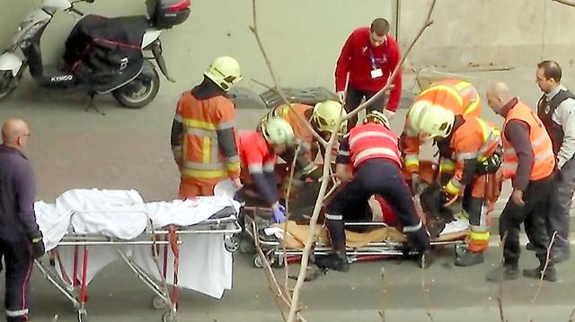 爆発があったブリュッセルの地下鉄駅の近くで22日、けが人を搬送する救急隊員=AP