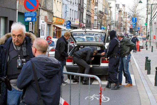 ブリュッセルの病院入り口前で23日、検問で車の中を捜索する警察官=AFP時事