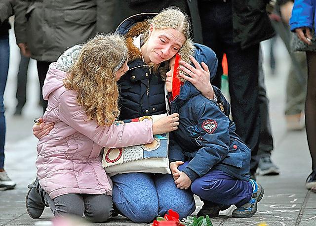 ブリュッセルの路上に設けられた追悼の場で23日、連続テロの犠牲者を悼む女性と子ども=ロイター