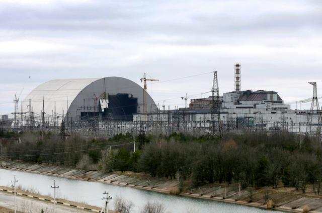 チェルノブイリ原発の「石棺」を覆う巨大なかまぼこ形の新シェルター(左)=杉本康弘撮影