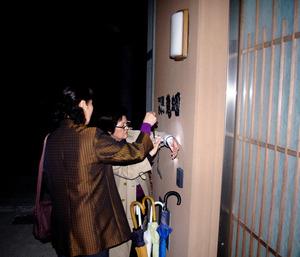 抜き打ち調査の開始直前、玄関前で腕時計を確認するUビジョン研究所の本間郁子理事長(写真奥)ら=3月、熊本県人吉市の特別養護老人ホーム「龍生園」