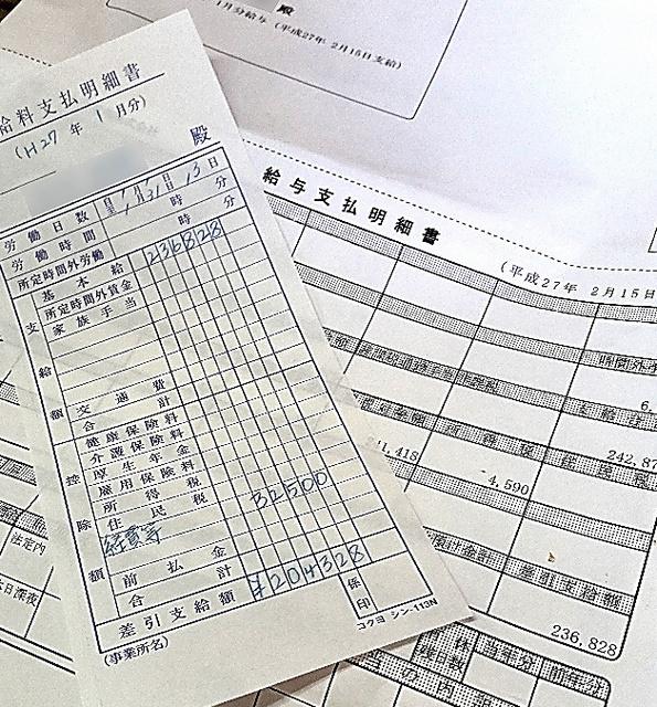 男性が毎月清掃業者から受け取った2枚の給与明細。水道管理会社が作った書類では、2015年1月分の支給額は23万6828円(右下)。清掃業者が作成したという手書きの明細では20万4328円(中央下)だ(写真の一部を加工しています)