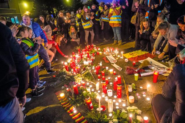 爆発テロのあったベルギー・ブリュッセルの空港近くで23日、空港職員たちが犠牲者を悼んでろうそくに火をともした=AFP時事