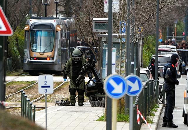 ブリュッセルのスカルベーク地区で25日、発見された不審物のそばに立つ爆発物処理班とロボット=AFP時事