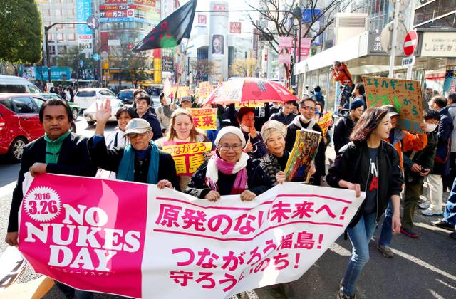 反原発を訴えるデモで、「原発のない未来へ」などと書かれた横断幕を掲げながら街中を歩く人たち=26日午後3時11分、東京都渋谷区、関田航撮影