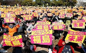 反原発集会に集まり、「つながろう福島」などと書かれたメッセージを掲げる人たち=26日午後2時32分、東京都渋谷区