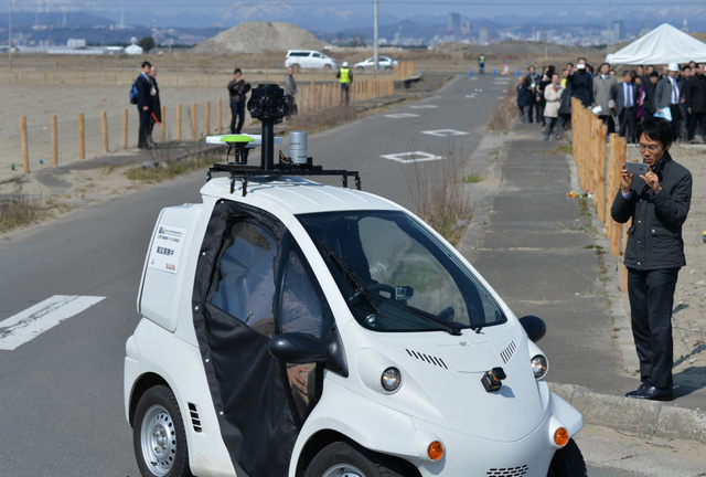 災害危険区域の市道であった自動運転の実証実験。人が乗っているが、ハンドルは握っていない=27日午前、仙台市若林区、福留庸友撮影