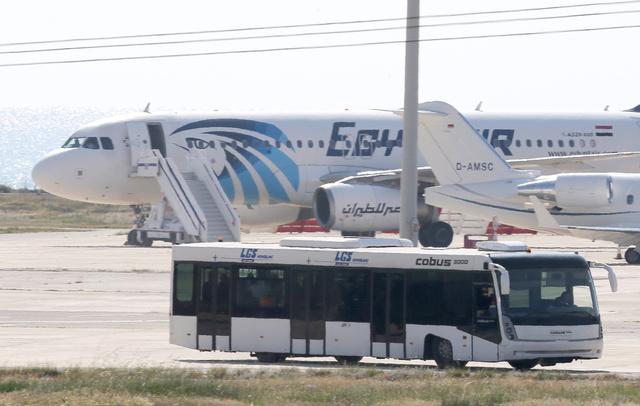 キプロスのラルナカ空港で29日、ハイジャックされたエジプト航空機(後方)からバス(手前)で一部の乗客らが解放された=AP