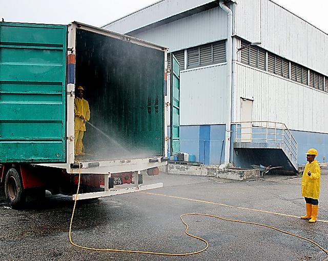 マレーシアの物流拠点でトラックを宗教洗浄する作業員=日本通運提供