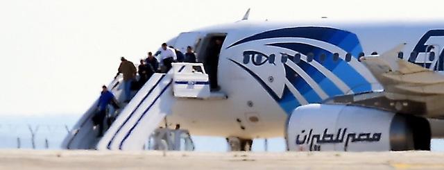 キプロスのラルナカ空港で29日、ハイジャックされた旅客機から降りる乗客ら=AFP時事