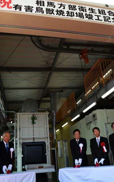 イノシシ専用焼却施設の火入れ式でスイッチを押す立谷秀清・相馬市長(右から2人目)ら関係者=相馬市光陽3丁目