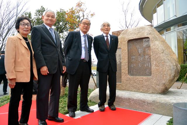 「新潟水俣病の歴史と教訓を伝える碑」とともに並ぶ被害者と弁護士=新潟市北区