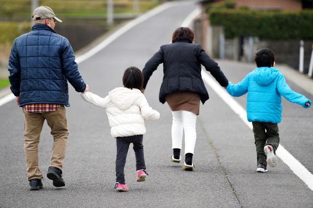 一家で散歩。兄妹は田や花を見ようと夫婦の手を引く=香川県、伊藤進之介撮影