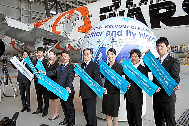 ANAホールディングスの新入社員らは、片野坂真哉社長(右から5人目)と飛行機の前でポーズ=1日、羽田空港