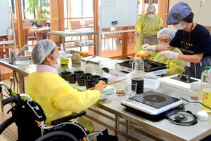 車いすに座り、調理や盛りつけをする利用者ら=徳島市津田本町2丁目の「つだまちキッチン」