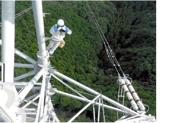 鉄塔にのぼって送電線などの確認を行う九電ハイテックの社員=同社提供