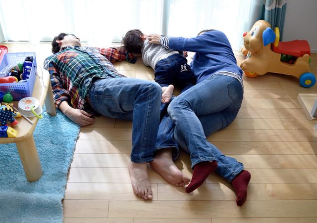 居間で遊びながら寝転がる親子=伊藤進之介撮影
