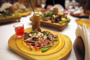 おつまみとして出された、豚の脂身などが盛られた一皿。西洋わさびが添えられ、左のグラスには、ウォッカベースの「クリュクバのナストイカ」が注がれていた=ミンスク、杉本康弘撮影