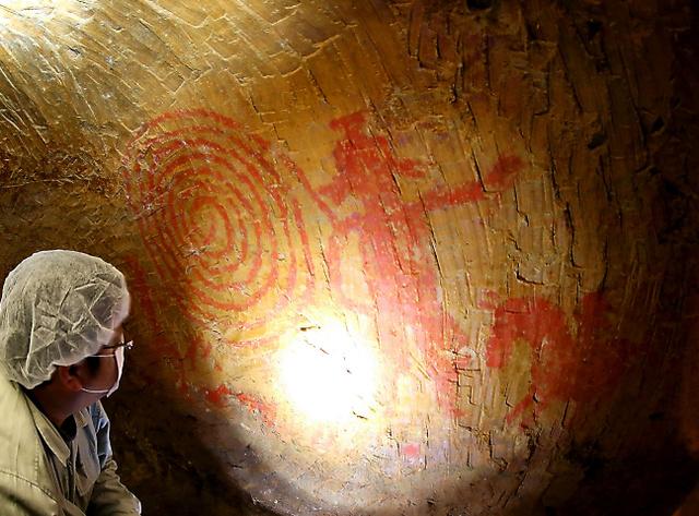 文化庁職員らによる渦巻文や人物などが描かれた清戸迫横穴の壁画の調査(魚眼レンズ使用)。渦巻文の付近に塩分の結晶とみられる白い物質が浮き出ていた=2014年4月、福島県双葉町、関田航撮影