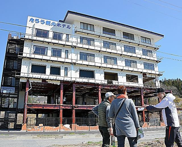 「たろう観光ホテル」の前でガイドから被災の状況を聞く人たち