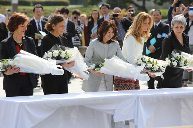 平和記念公園を訪問、原爆死没者慰霊碑に献花する岸田裕子・外相夫人(中央)と各国の外相夫人ら=10日午後2時59分、広島市中区
