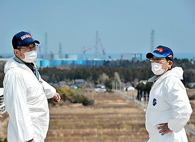 高台から東京電力福島第一原子力発電所を見下ろす岡田さん(左)と中島さん