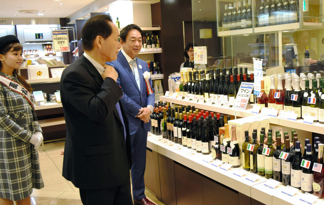 各国のワインが並ぶ売り場を見学する浜田恵造知事(手前)=高松三越