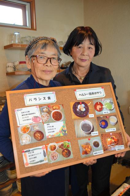 メニュー例のボードを持つ祖父江鈴子さん(右)と五十嵐桂葉さん=岩倉市