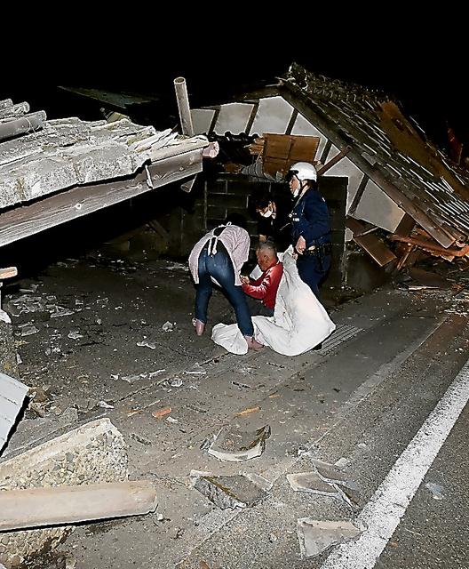 倒壊した家屋の前で座り込む人たち=14日午後11時22分、熊本県益城町、いずれも福岡亜純撮影