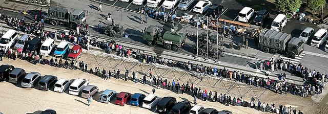 避難所では、自衛隊の給水などを待つ人の長い列ができていた=17日午前7時50分、熊本県益城町、本社ヘリから、高橋雄大撮影