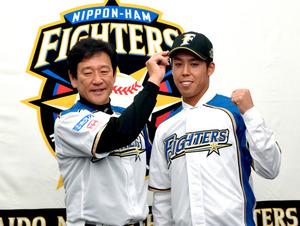 入団記者会見で、栗山監督(左)に帽子をかぶせてもらう大累