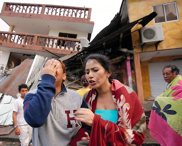 エクアドルのペデルナレスで17日、地震で倒壊した住宅の前で泣く女性ら=AP