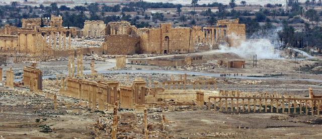パルミラの古代都市遺跡。過激派組織「イスラム国」(IS)が一部を破壊したベル神殿(奥)近くで、ロシア軍の地雷除去作業による煙が上がっていた=14日午前、シリア・パルミラ、矢木隆晴撮影