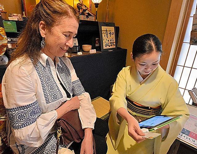 スクエアの端末がついたタブレット端末で支払いを済ませる外国人観光客(左)=3月下旬、京都市
