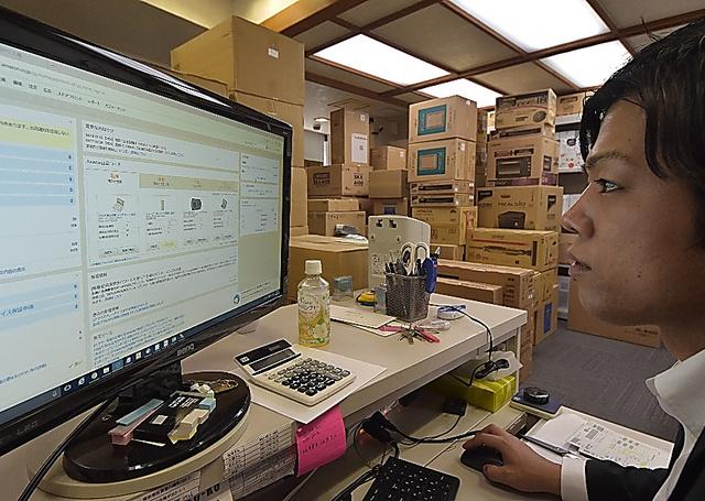 事務所でパソコンに向かう松本尚也。出店するアマゾンからの融資で事業を拡大させている=大阪市浪速区
