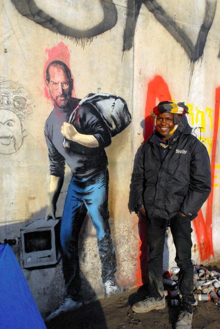 バンクシーが描いた「シリア移民の息子」と、モハメド・イブライムさん=仏北部カレー、高久潤撮影