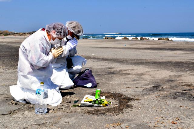 津波に襲われた海岸で手を合わせる関根さん(左)と森さん=双葉町中浜